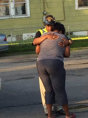 A woman weeps in the arms of a Ten Point Coalition member at a shooting scene Friday, July 8, 2016, in the 900 block of North Oxford Street.