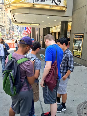A group of Pokemon Go players stop on a sidewalk at 53rd and Broadway in New York.
