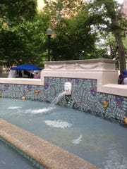 A mosaic fountain in Rittenhouse Square, a park and hangout in Center City Philadelphia. Kids cool off in the pool, teenagers and adults sit on the concrete ledge.