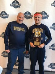 Schoolcraft freshman Eric Wilkewitz shares his championship moment with Ocelots cross country coach Wright Wilson.