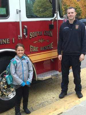 Lily Burnside with South Lyon Deputy Fire Chief Mike Weir.
