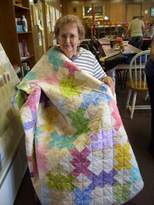 Betty Gunson displays the quilt she won in a drawing at The J.D. Lewis Senior Citizens Center.