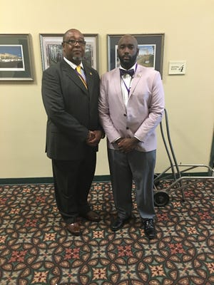 Alvin Jackson (left) and his son Alonzo Jackson proudly wear shades of purple and gold, reflecting their membership in the Omega Psi Phi fraternity. The men credit the brotherhood for making their family ties even stronger.