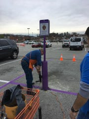 Employees work to install 'Purple Heart' priority parking outside Jackson's Home Depot.
