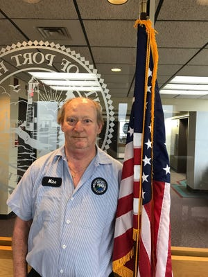 Vietnam veteran Mike Young stands with an American flag. Young will be helping the city in managing flag disposal services.
