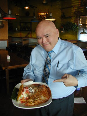 General manager Gabriel Chavez presents one of Que Pasa's combination taco and enchilada plates.