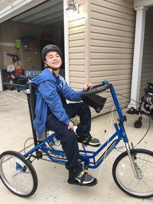 Dominic Stratton, 15, of Mount Laurel is shown on the adaptive bike bought by donors.