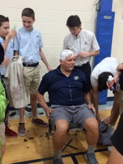 Saint Michael Lutheran School boys basketball coach Bob Schaaf gets his head shaved during a ceremony celebrating his team's national championship. Schaaf said he'd get his head shaved if the team won the title.