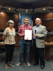 Marcel Adolf receives an honorary citizen award from former Abilene mayor Norm Archibald. Paulette Haught, left, was Adolf's English instructor.