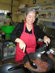 Chol Hauschel uses a wok to cook a batch of spicy pork.
