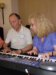 Joe Augusta plays the keyboard with Melinda Burgard.