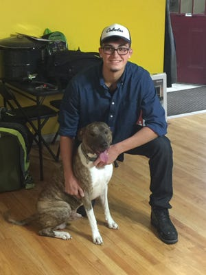 Christopher Knight Jr., of Lansing, cuddles his dog, Rello, in a family photo. Knight, 23, died Wednesday after a motorcycle crash.