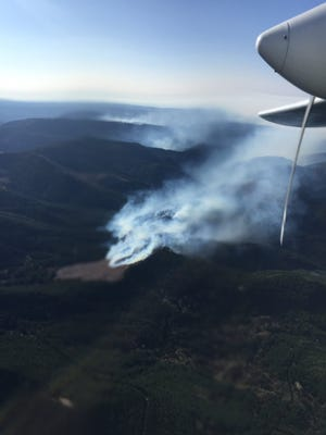 Winds reignited at least nine slash burns in the Cascade foothills Monday.