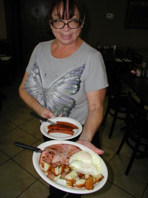Bekki Cunningham heads to a customer with a half-order of ham and eggs. She's a server and wife of chef Danny Cunningham.