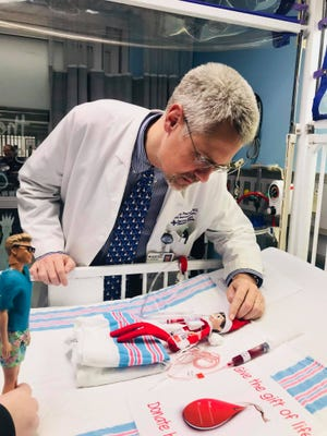 """Pediatric neurosurgeon Dr. Matthew Pearson consults injured Elf on the Shelf """"Code'y"""" as Nurse Spencer stands ready to aid."""