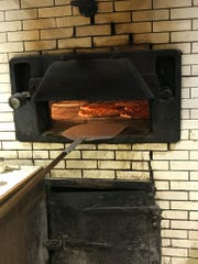 The same brick bread oven from 1917 is still used today at DeLucia's Brick Oven Pizza.