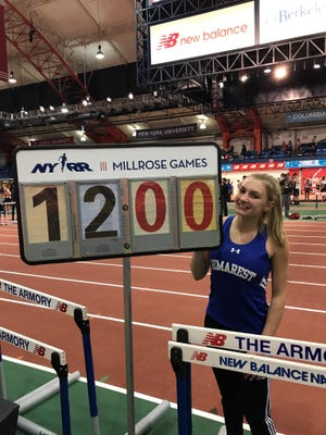 Sydney Woods of NV/Demarest proudly displays the scoreboard showing her personal best clearance of 12 feet at the Tim St. Lawrence Invitational on December 15, 2017. She is the seventh girl in North Jersey history to clear the height.