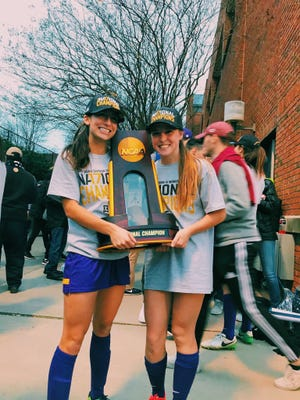 Sarah Scire (left) and Sarah Kelly posing with Division III women's soccer championship trophy.