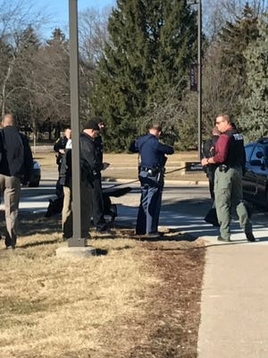 Authorities gather on the campus of Central Michigan University during a search for a suspect, in Mount Pleasant, Mich., Friday, March 2, 2018.