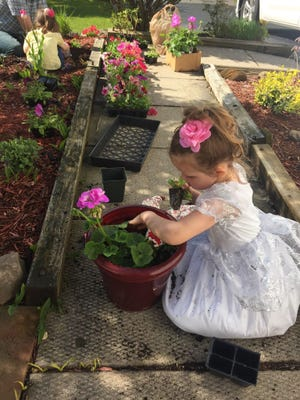 Avery Bartz, 5, of Chili and sister Tessa, 3, plant flower beds on Mother's Day 2017. A family outing to purchase gardening supplies and creating a garden is how the Bartz family spends each Mother's Day.