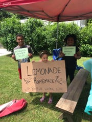 Kayden (left), Ava (center) and Josslyn Linquist hold signs advertising lemonade on Saturday, June 2. The children gave $50 to their neighbor, Quentin Fox, to help him repair his property damaged by floods.