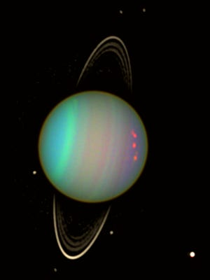 Uranus's faint rings and several of its moons are visible in this image taken from the Hubble Space Telescope in 2004. A new study suggests the planet's odd tilt was caused by a cataclysmic collision with another object 4 billion years ago.