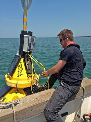 Ed Verhamme, a project engineer at LimnoTech, works on an environmental data buoy used to track Lake Erie's water quality.