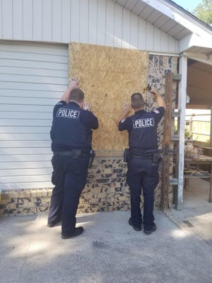 Police board up the house at 5804 Enid St. as part of the abatement process.