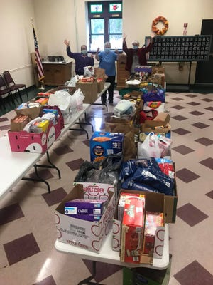 Volunteers sort through donations gathered at Millbury First Congregational Church's drive-by donation collection Oct. 3, 2020, for the food pantry at the Millbury Senior Center.