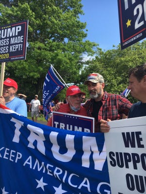 Charlie Chase, center in red hat, who was assaulted while holding a Trump sign on Tuesday, was joined at the site of his attack on North Main Street at the Airport Road rotary Saturday, June 6, by people in support of him and the Trump campaign.