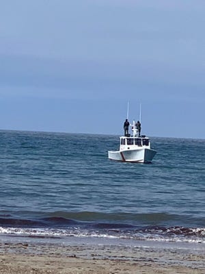 A crew checks the White Horse Beach area after a confirmed shark sighting Saturday afternoon.