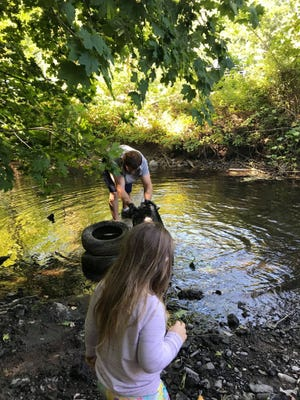 Taunton resident Alex Whittaker has been taking his two children, 9-year-old Sam and 4-year-old Olivia, to clean trash out the Mill River behind Manny's Paint and Hardware in Taunton.