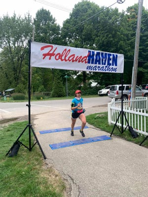 A runner finishes the Holland Haven race on Saturday.