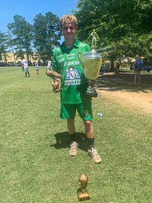 """Former GWU soccer player Preston """"Petey"""" Walker poses with the  Golden Boot and Championship trophies after leading Leon FC to a title."""
