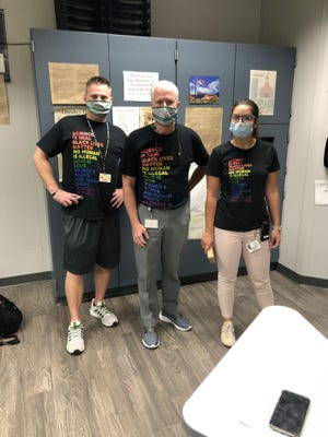 This photo of, from left, Dublin Scioto High School social studies teacher Scott Marple, Principal Bob Scott and assistant Principal Leanndra Yates stirred controversy and an indirect rebuke from the superintendent of Dublin schools because of the statements on their shirts.
