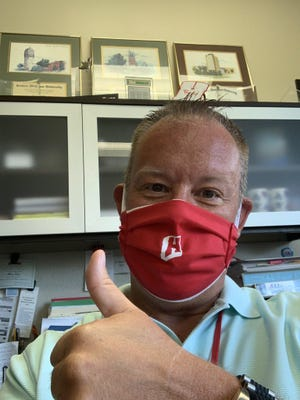 """Holland Public Schools superintendent shows off a face mask featuring the district's """"Power H"""" logo."""