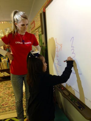 St. Frances Cabrini School first-grader Liliana Calderon works a math problem with her teacher Kim Swart on Friday, Nov. 21. The school uses TouchMath curriculum in its lower grades.