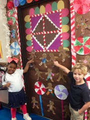Parker Martin (left) and Braxton Jones point to the gingerbreadmen they decorated in Leah Palmer's pre-kindergarten class at Cherokee Elementary. They learned about the five senses as they completed the project, which is part of a door-decorating contest at the school.