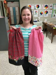 Rapides High librarian Crystal Mallett displays two dresses made by the Beta Xi chapter of Delta Kappa Gamma as a service project. The dresses will be shipped to children in Africa through the nonprofit Little Dresses for Africa.