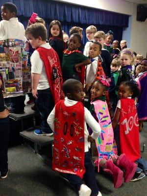 Peabody Montessori Elementary School first- and second-graders show off their capes in celebration of the 100th day of school on Friday. Each student decorated a re-purposed shirt or pillowcase with 100 items. Students got creative with candy wrappers, sequins, basketballs and more.