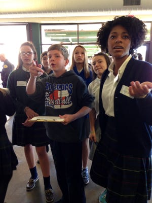 "Shawn Gailagher (center) and fellow members of ""Team Eagle,"" sixth-grade students from St. Frances Cabrini School and Our Lady of Prompt Succor School, work with Holy Savior Menard Central High School student leader McKenzie Seastrunk (right) from to answer a question on the school-wide scavenger hunt on Monday. The welcoming event serves as a tour of the school while focusing on the value of Catholic education for National Catholic Schools Week."