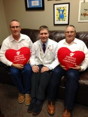Twins Dennis (left) and Daniel Decuir (right) of Marksville each had quadruple bypass surgery last year to address coronary artery disease. Heart catheters revealed the twins had blockages in the exact same locations, cardiologist Dr. Michael Smith (center) said.