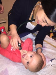 Dr. Stephanie E. Chin listens to Chace Bailey's heartbeat. The boy was born missing an artery between his heart and lungs.