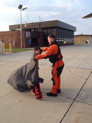 Petty Officer 3rd Class Derek Johnson, an aviation survival technician from Air Station Traverse City, Mich., wraps a blanket around Zachary Suri at the Menominee-Marinette Twin County Airport in Menominee, Mich., on Friday. Suri, along with his mother and cousin, were rescued from Whaleback Shoal in Green Bay after being stranded on the water overnight when their kayaks went adrift. (U.S. Coast Guard photo courtesy of Cmdr. Shad Soldano)