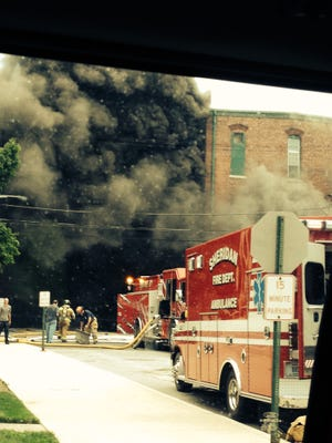 Crews battle a large fire July 12, 2014, on Main Street in downtown Sheridan, Indiana.