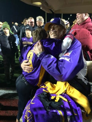 John Padgett, coach of the champion Vikings in the Washington Township Youth Football League, hugs player Connor Essick, 10.