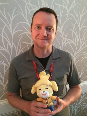 Bill Trinen, director of product marketing at Nintendo of America, holds a plushie of Animal Crossing character Isabelle.