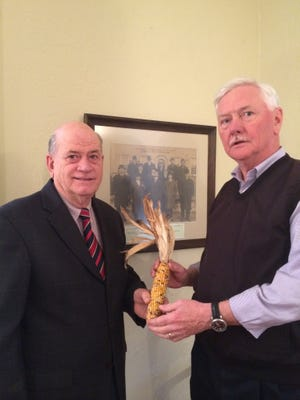 Trustees of the New Castle Common President Michael Alfree presents an ear of corn – the annual pay for serving on the panel – to the newest trustee, Thomas Episcopo.
