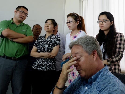 U.S. businessman Chip Starnes (sitting), who was held hostage for six days over a wage dispute, is surrounded by government officials and trade union leaders during a briefing at his Specialty Medical Supplies business in Huairou, Beijing on June 26, 2013.