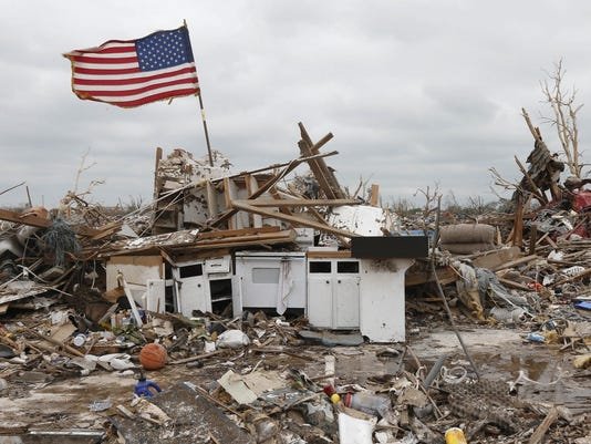 flag continues to fly amidst the remains of tornado destruction in Oklahoma
